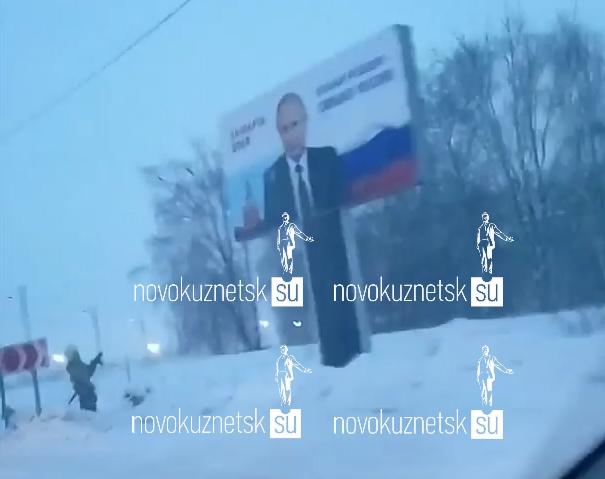 Пожарные моют баннер Путина, а полицейские охраняют