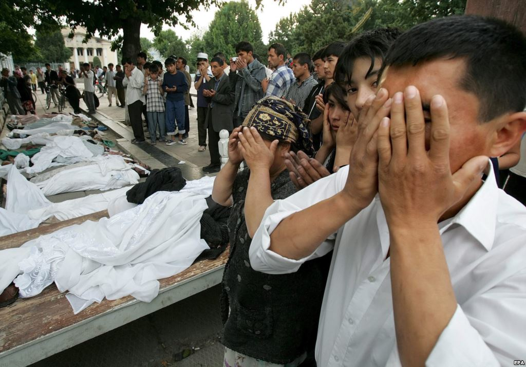 People pray on May 14, 2005, by the bodies of victims of the