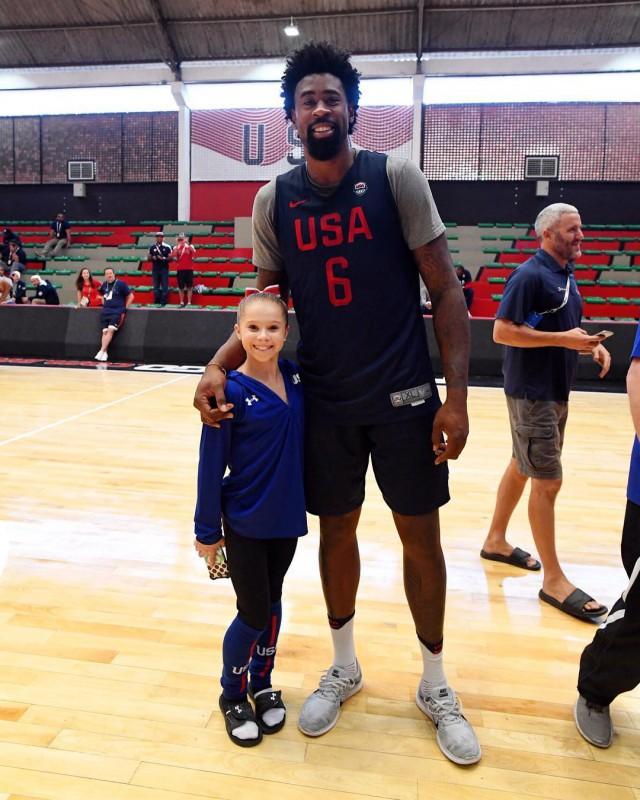 Олимпийская гимнастка позирует с баскетболистом.