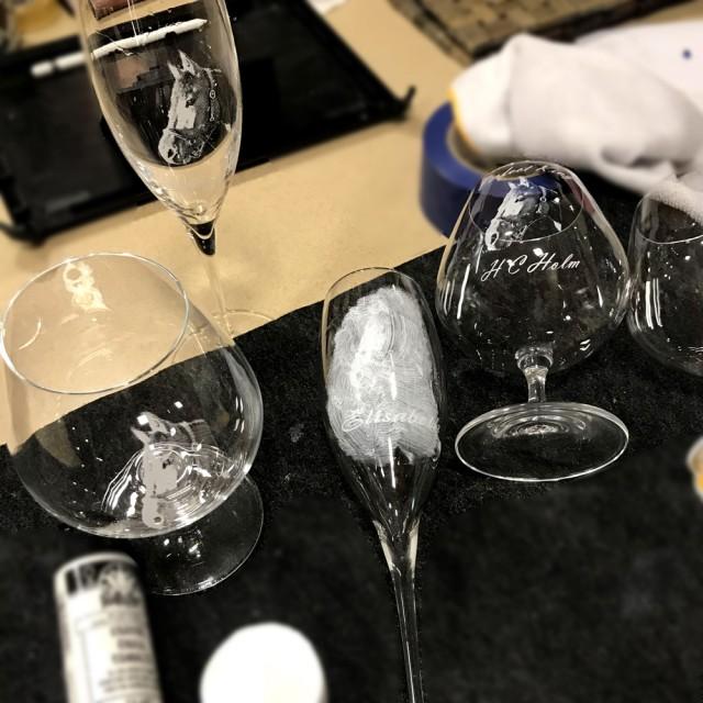 Процесс гравировки пескоструем на бокале шампанского